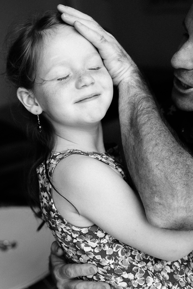 dad tenderly touches his daugther's face.