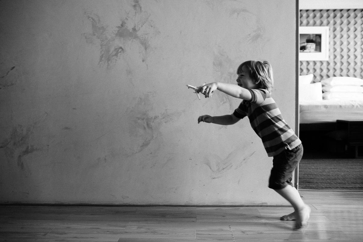 a boy runs along a wall with a toy plane
