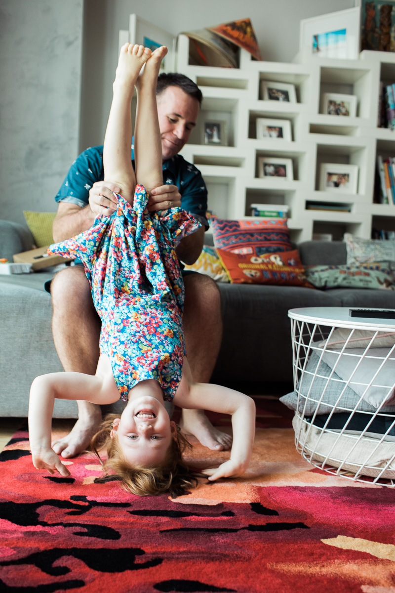 a father helps his daugther do handstands during a lifestyle family shoot.