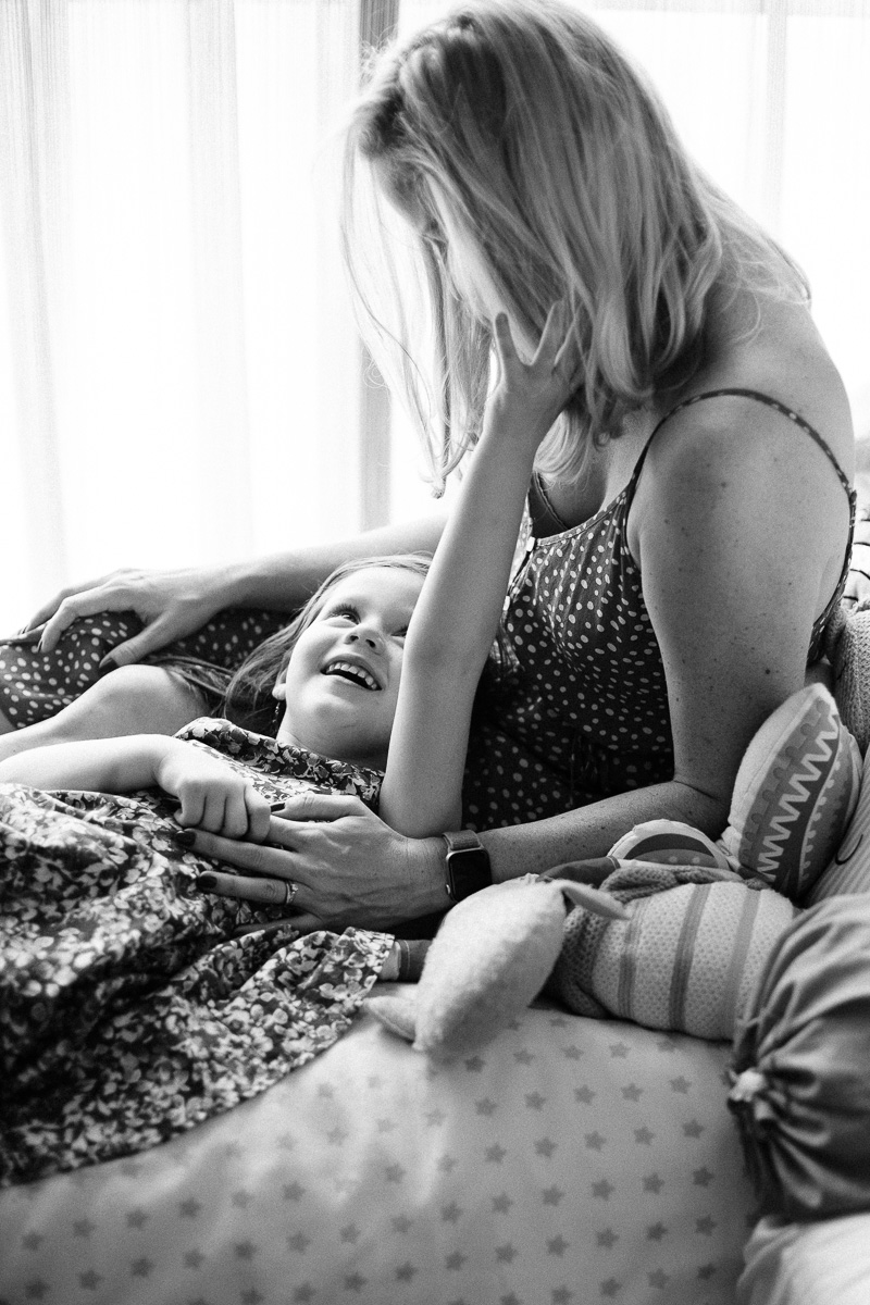 A daughter reaches towards her mother's hair