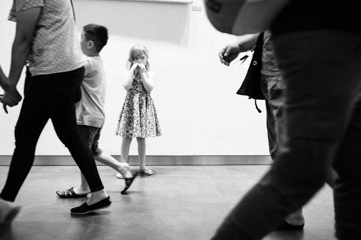 A black and white image of a little girl stands in a crowd in Jakarta