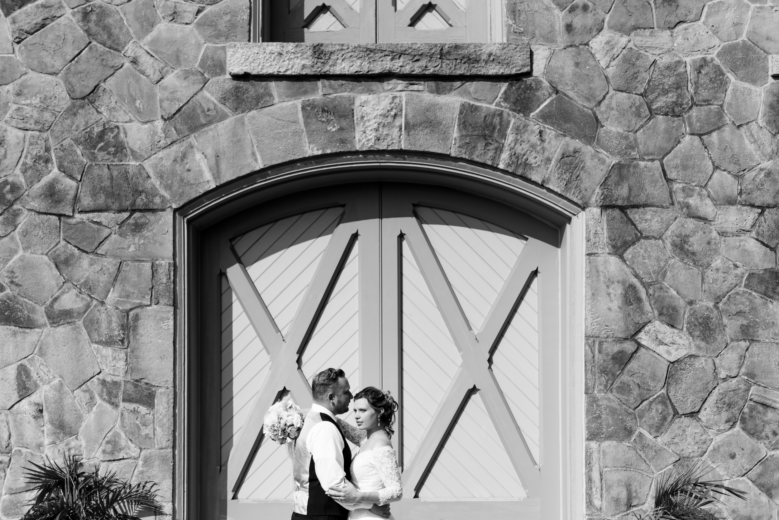 bride and groom on rock wall
