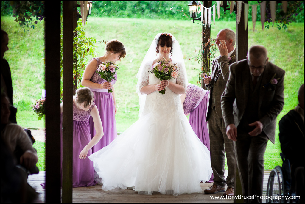 Safe at last. Bride's maids straighten Laura's dress whilst dad mops the rain from his face.