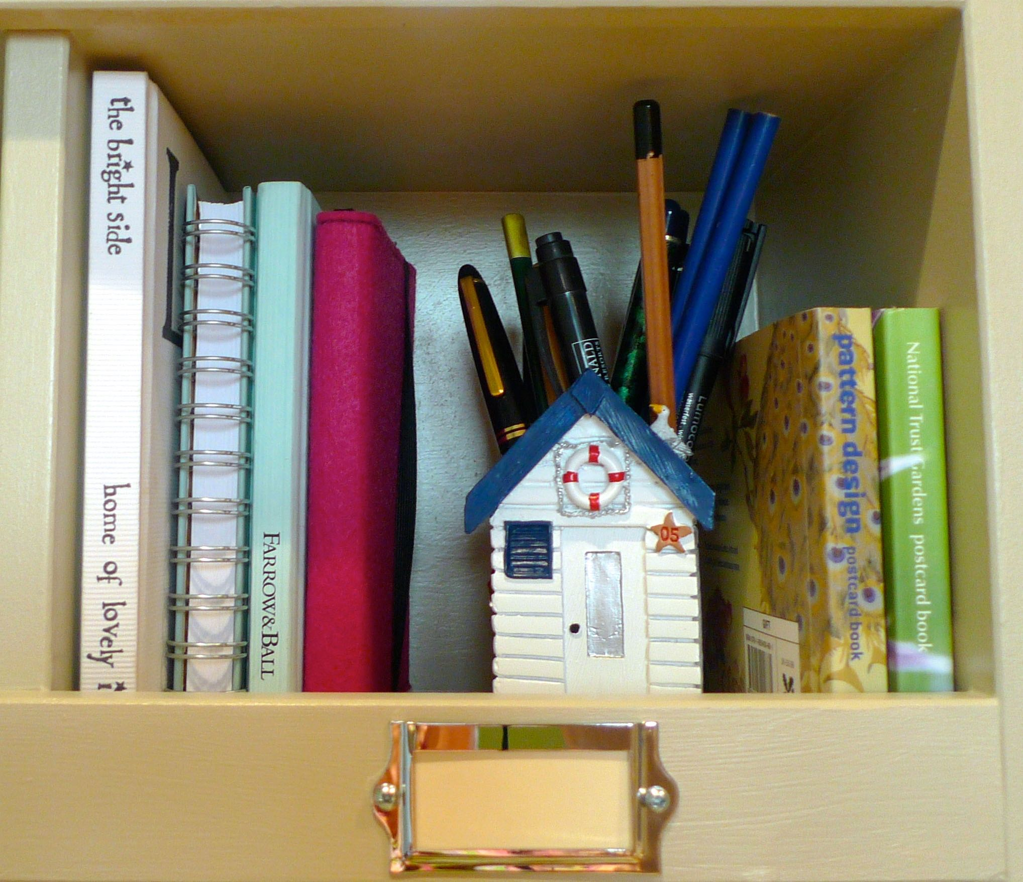 SOME NOTEBOOKS, POSTCARDS AND A POT FOR PENS