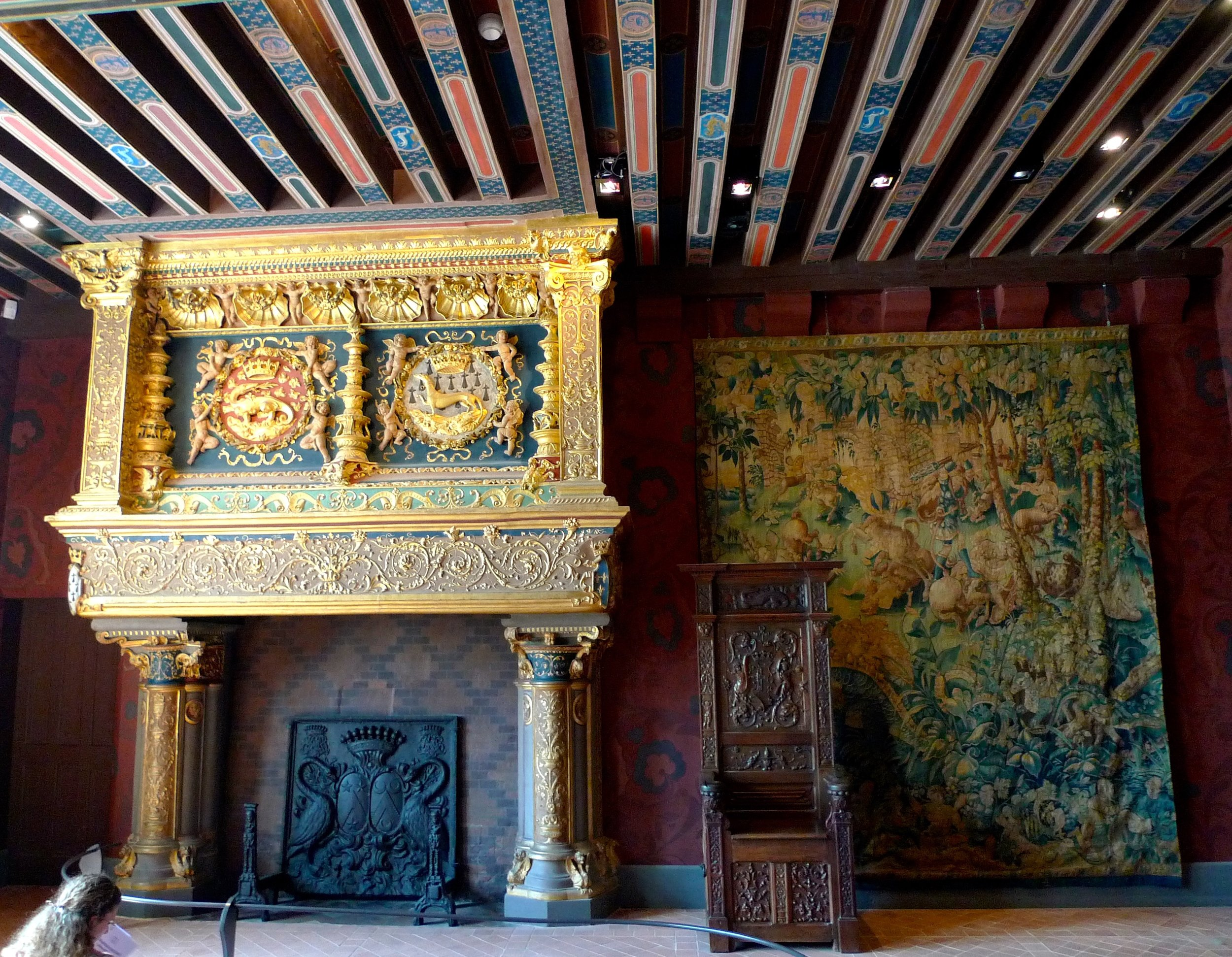 An ornate fireplace with a tapestry and a decorated ceiling