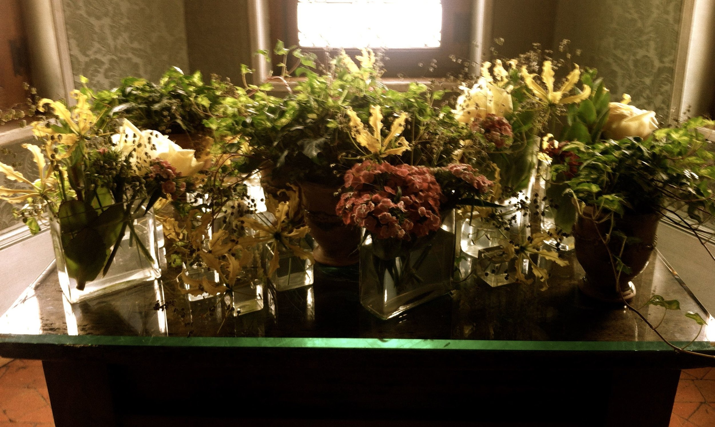 A desk full of flowers in the green study