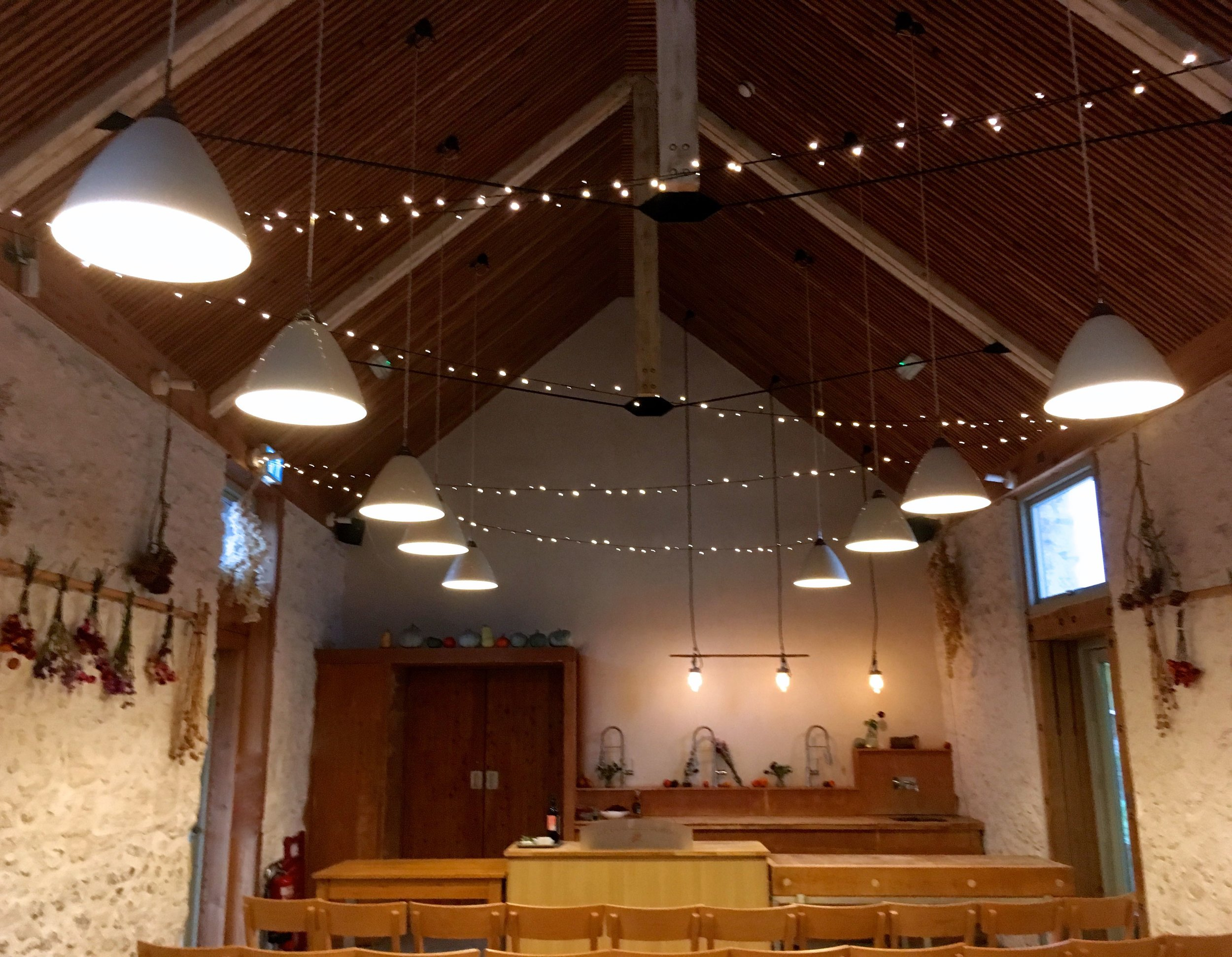 Inside the barn at River Cottage HQ with fairy lights in the gables