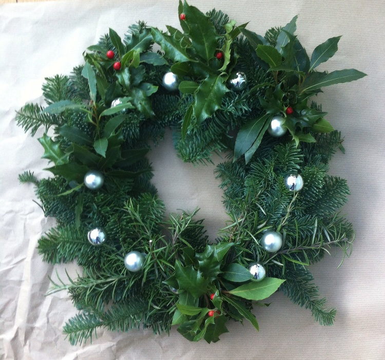decorate the wreath with baubles, holly, and herbs