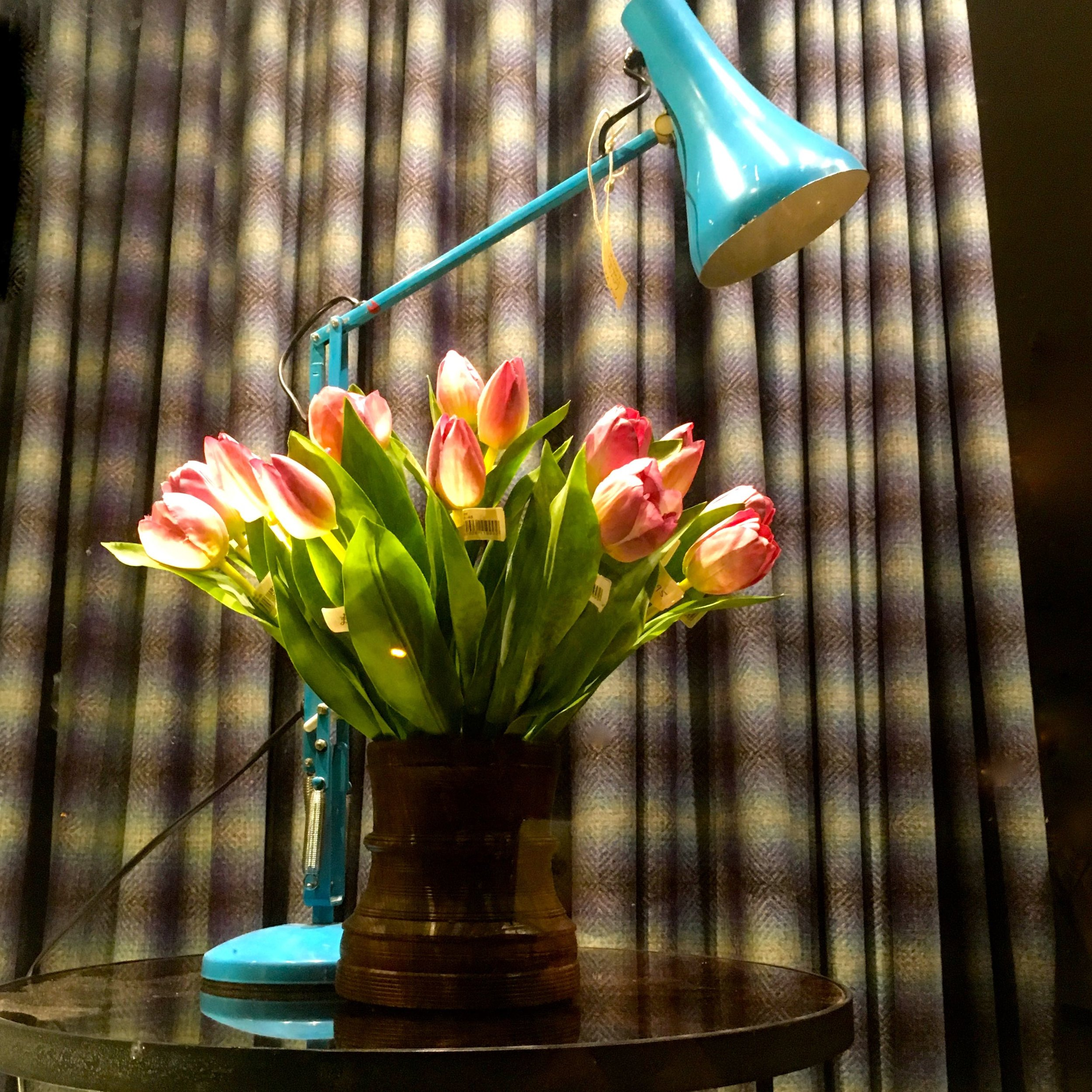 A turquoise anglepoise lamp and faux tulips, with a tartan curtain