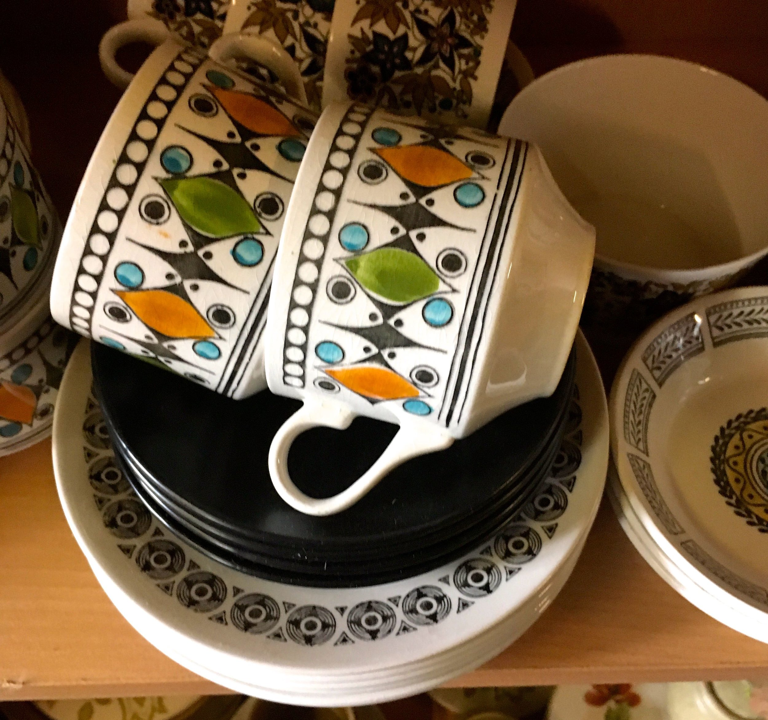 colourfully patterned tea cups, saucers and plates