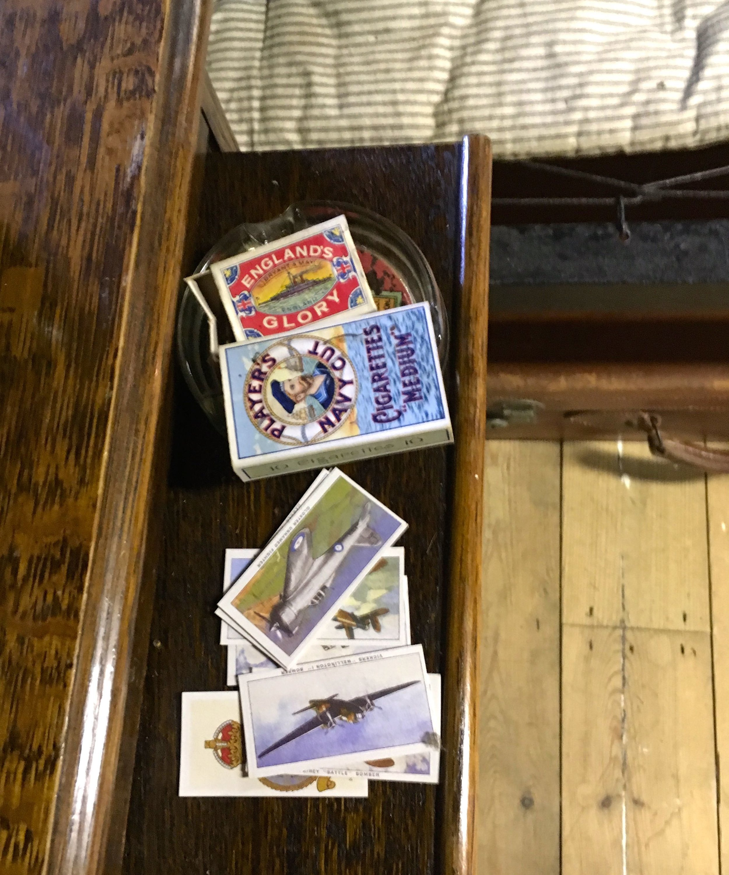 cigarettes, matches and cigarette cards on the bedside cabinet