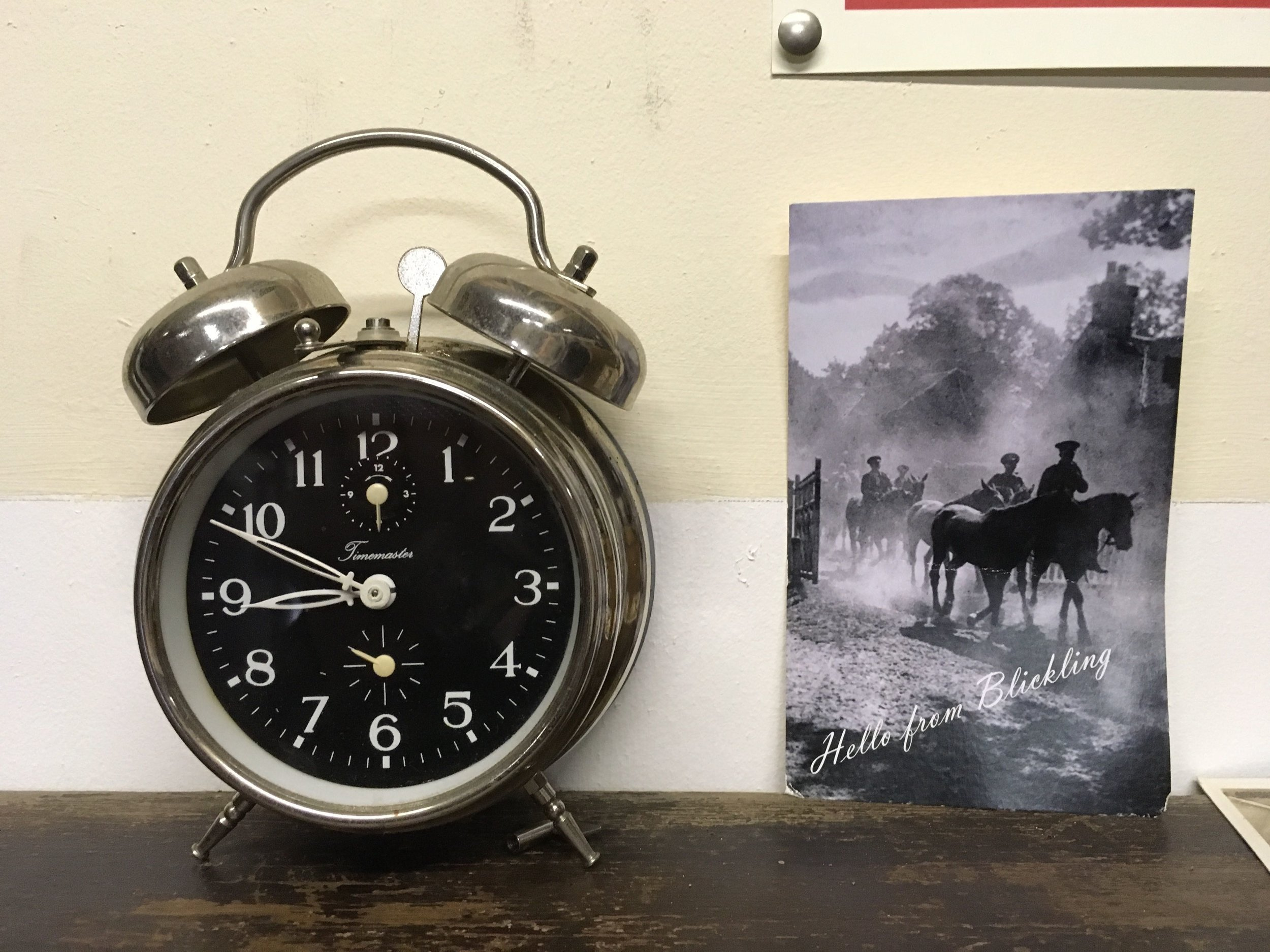 A traditional alarm clock and a Blickling postcard