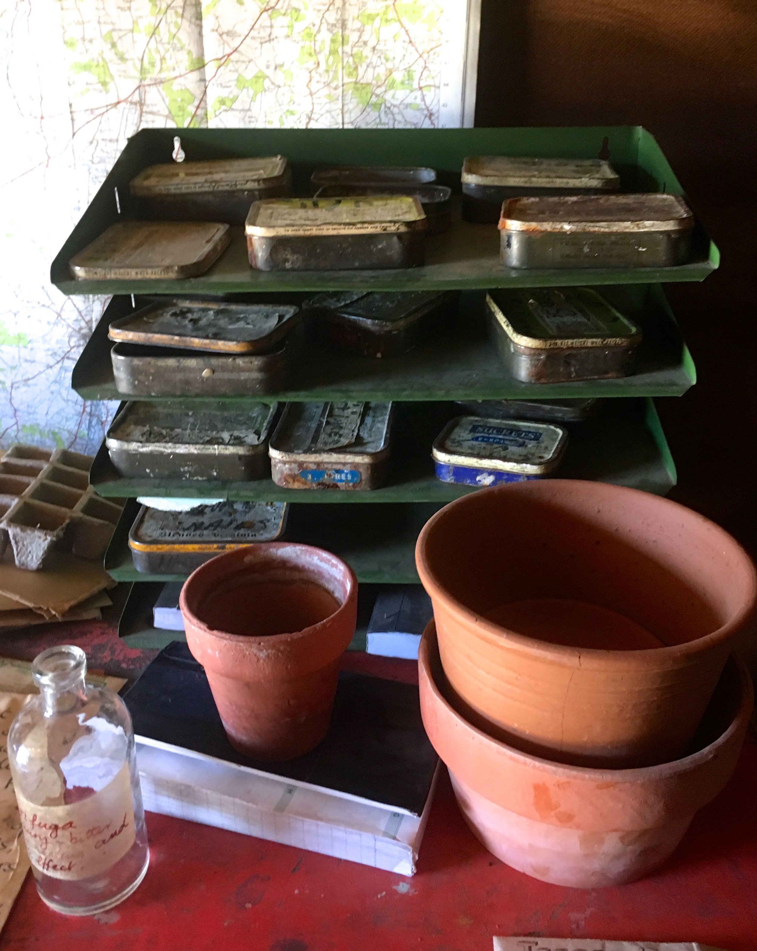 Old tobacco tins, no doubt storing seed, in the in tray and terracotta pots