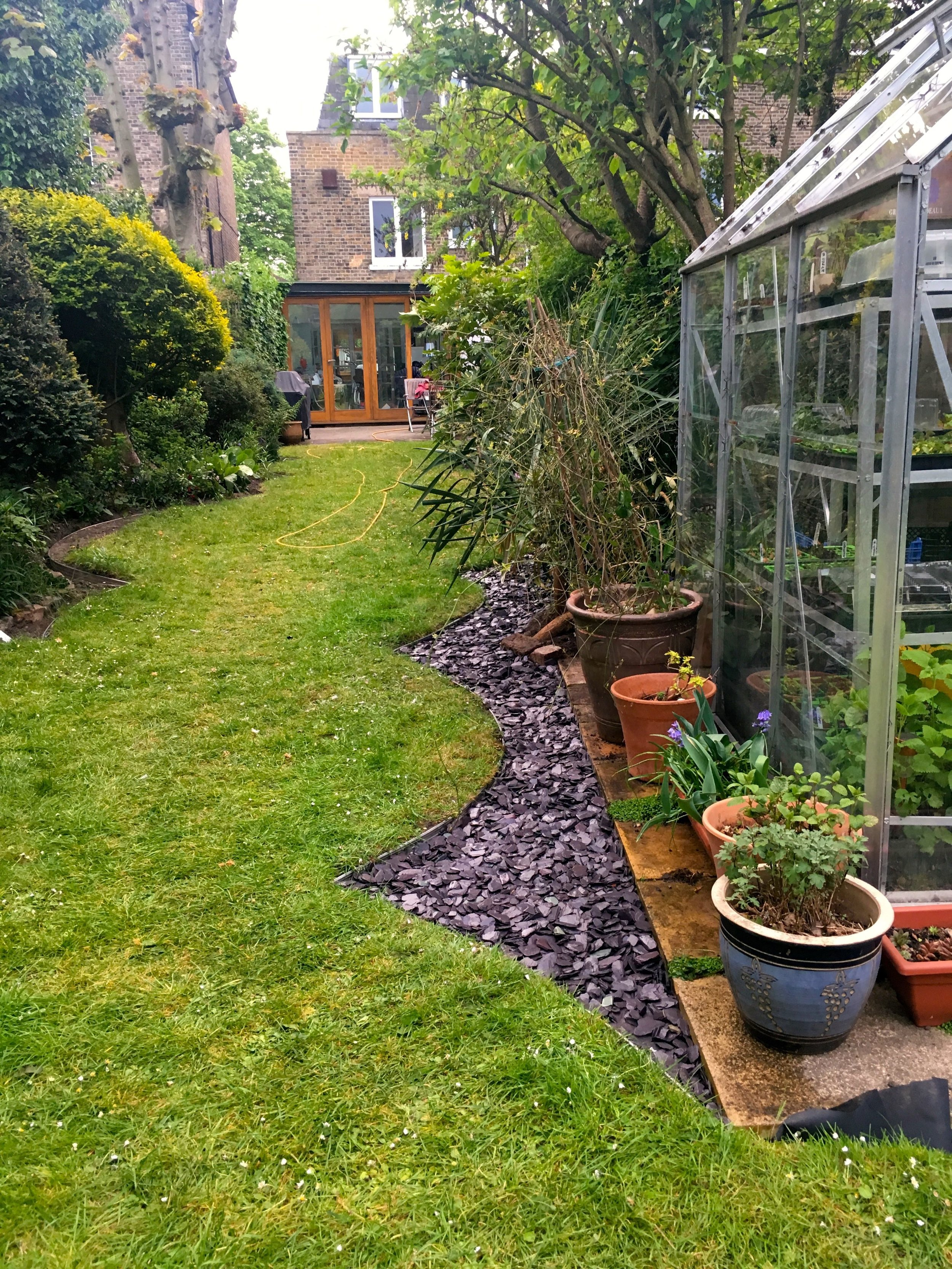 Looking down the garden towards the house, the slate is currently only on one side of the garden