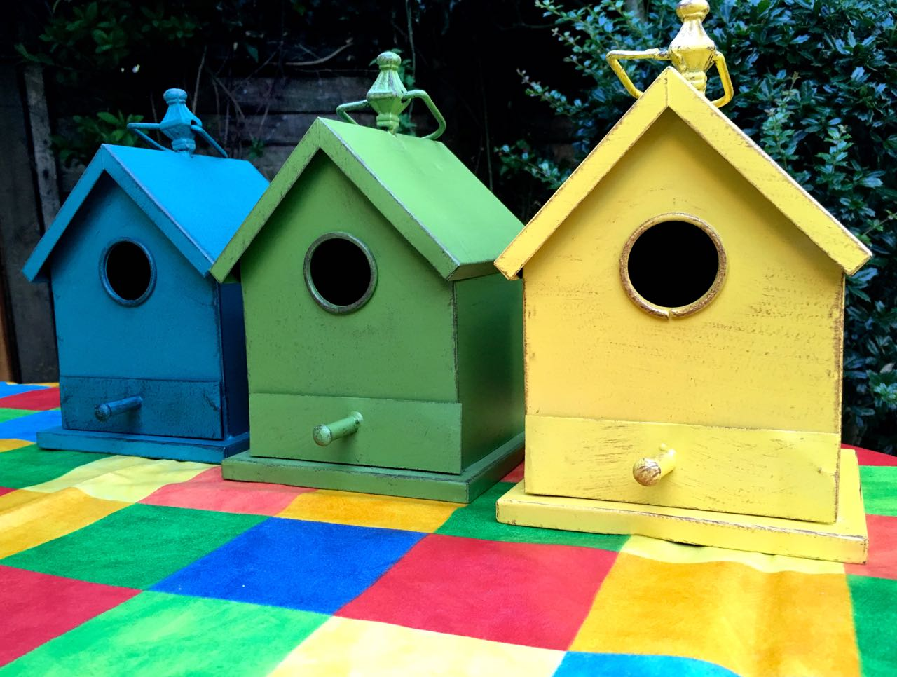 """A colourful """"estate"""" of bird houses from HomeSense ready to be deployed in the garden"""