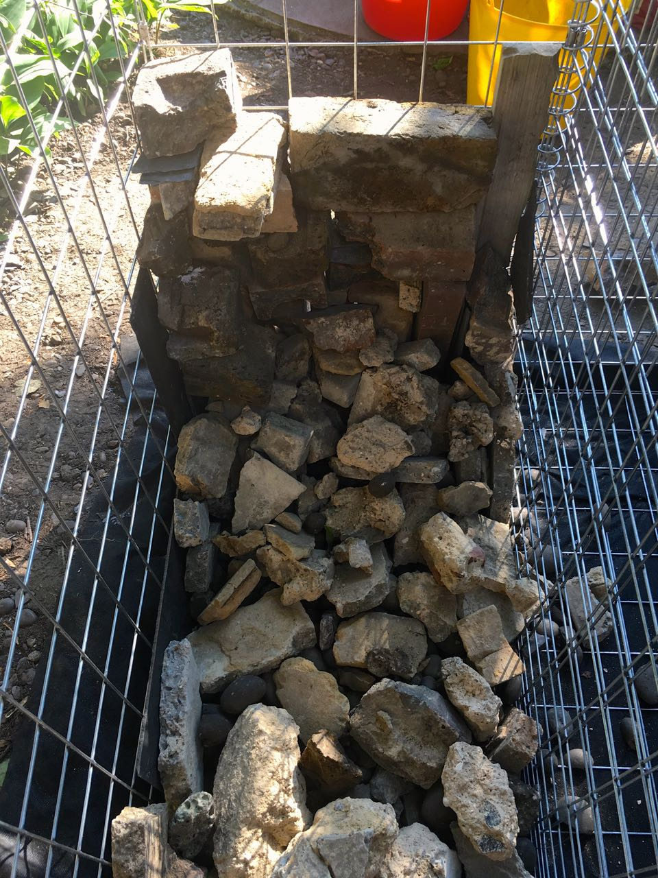 Starting to fill our gabion baskets with bricks and rubble sourced from freecycle