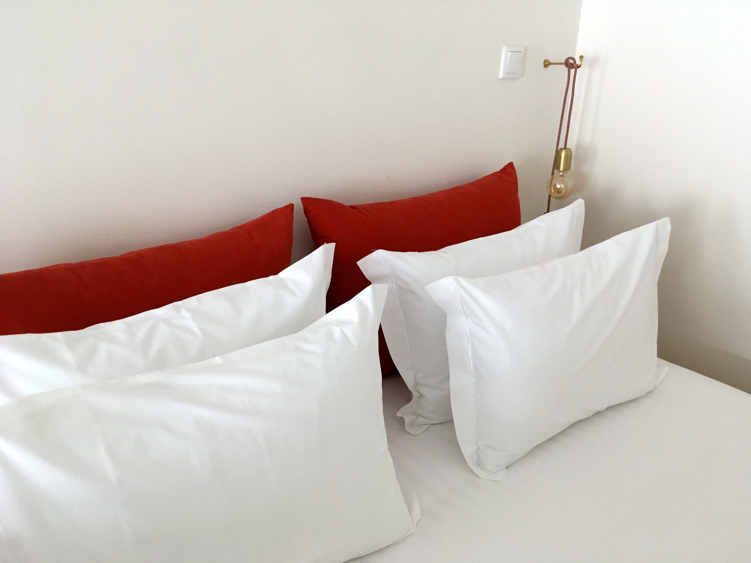 Stacks of cushions on a comfy bed in the quirky Porto apartment