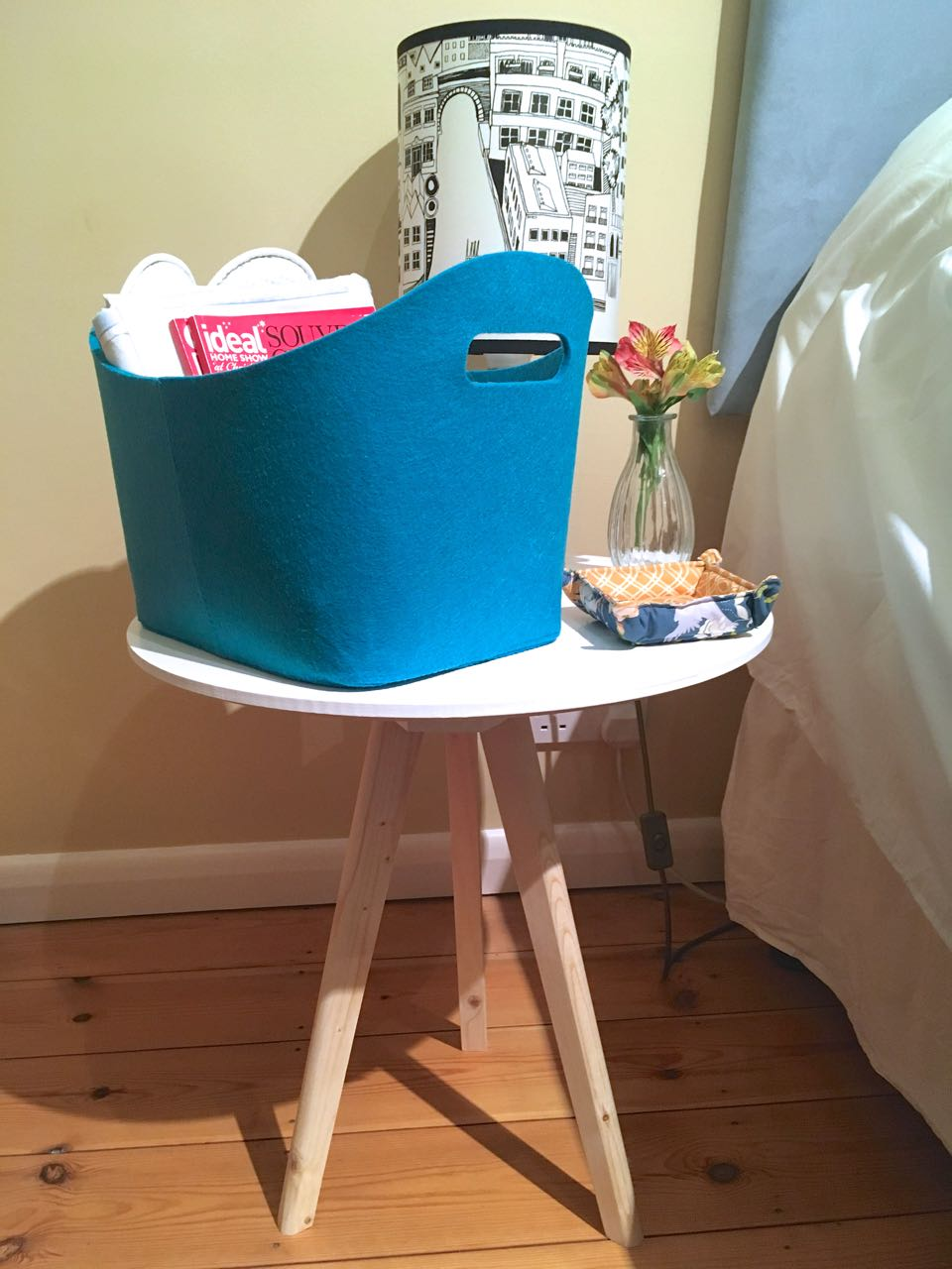 A simple side table as a bedside table complete with a zeller basket from wayfair full of goodies for my guests