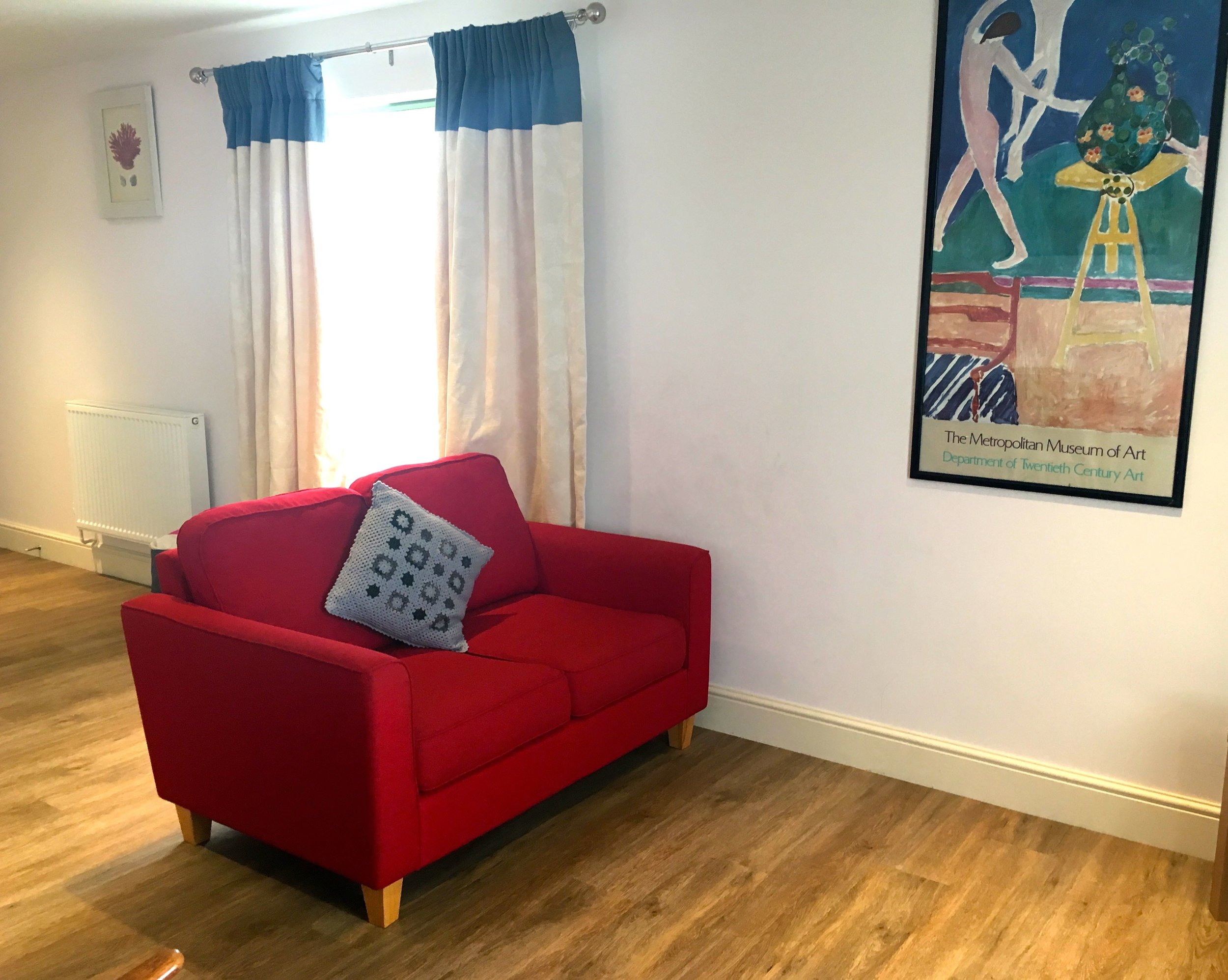 A kitchenette, two seater sofa and somewhere to sit