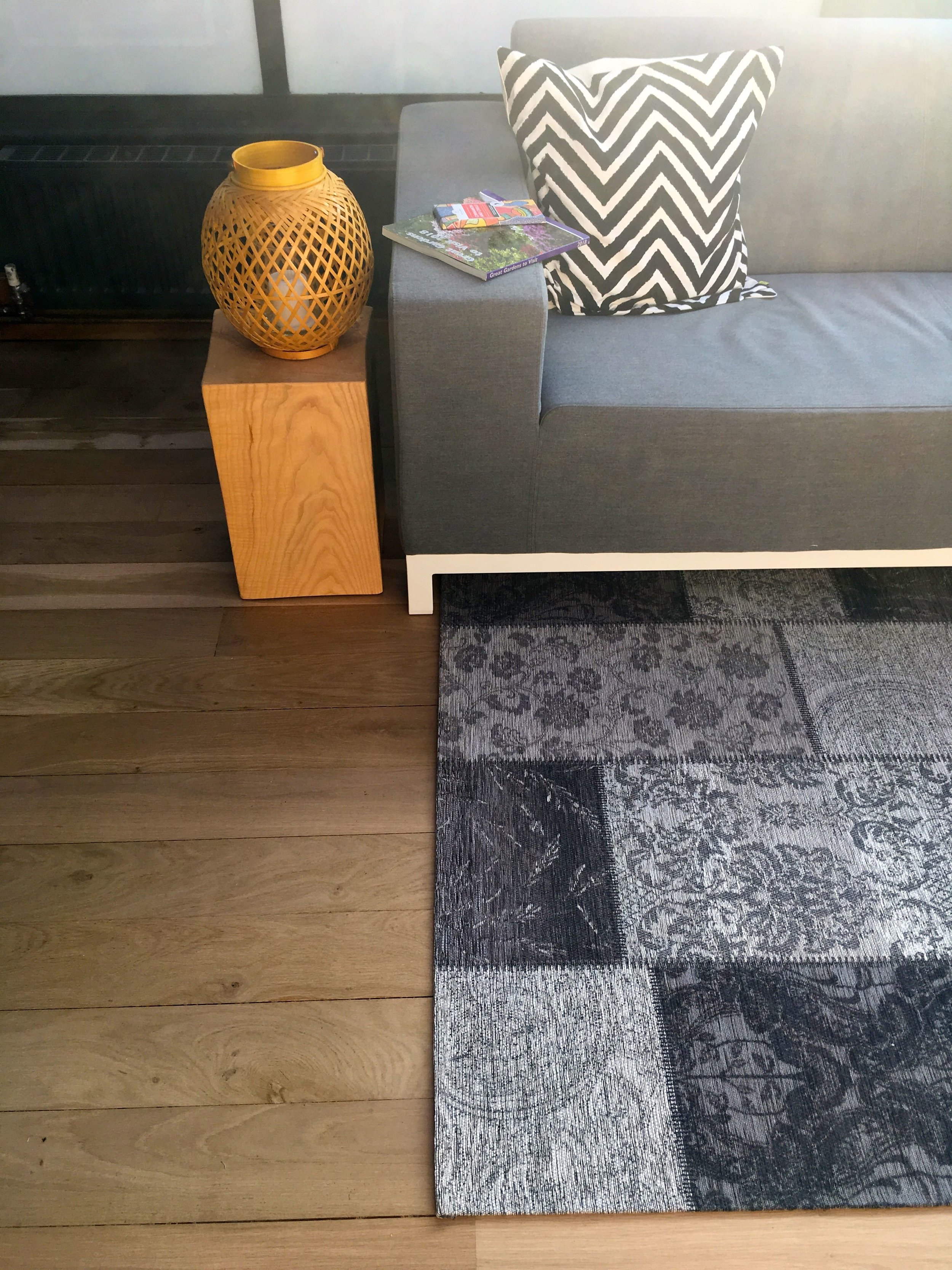 A head on shot of sofa, side table and a new patchwork rug