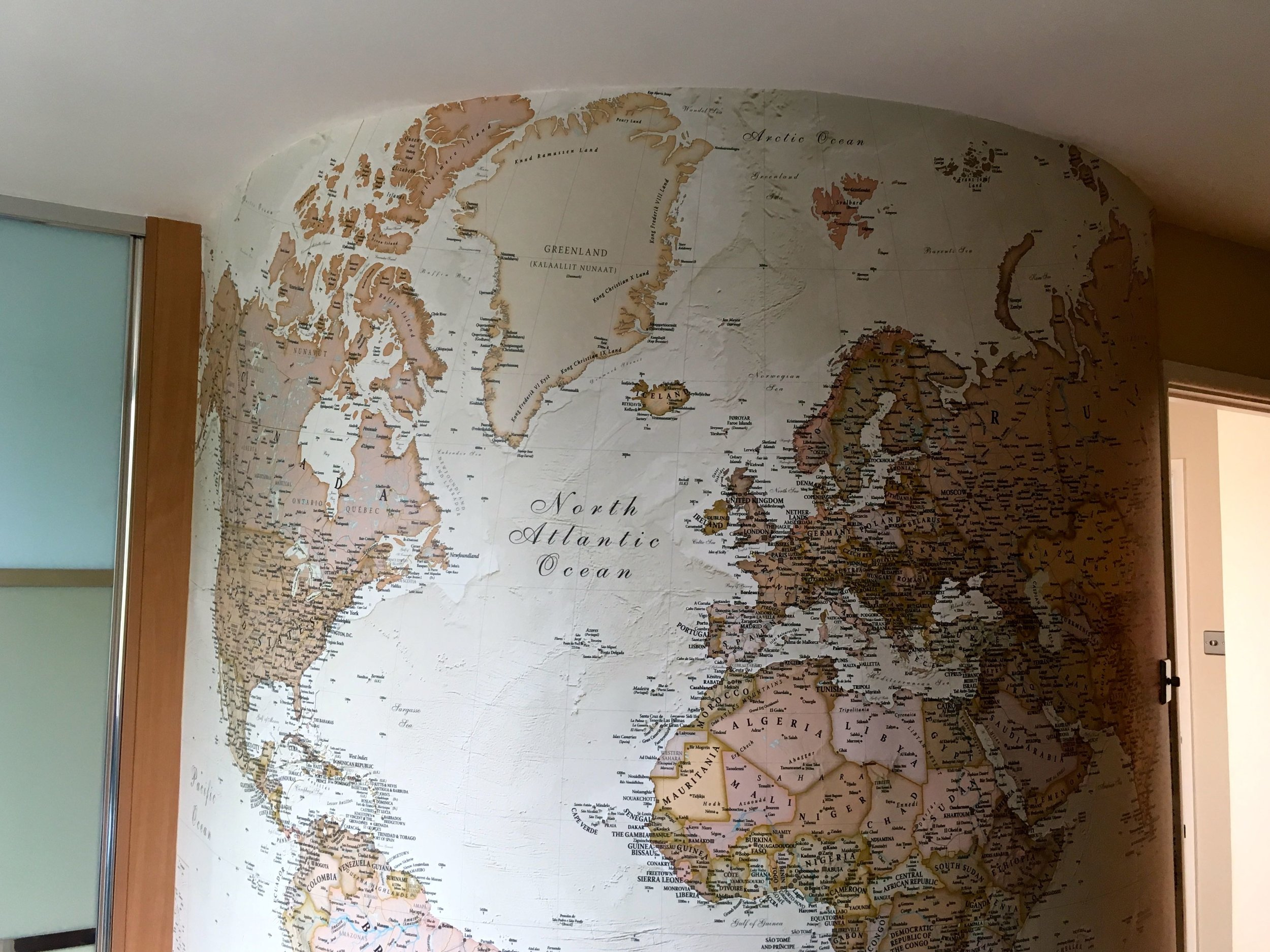 A map on a round wall has a globe life effect