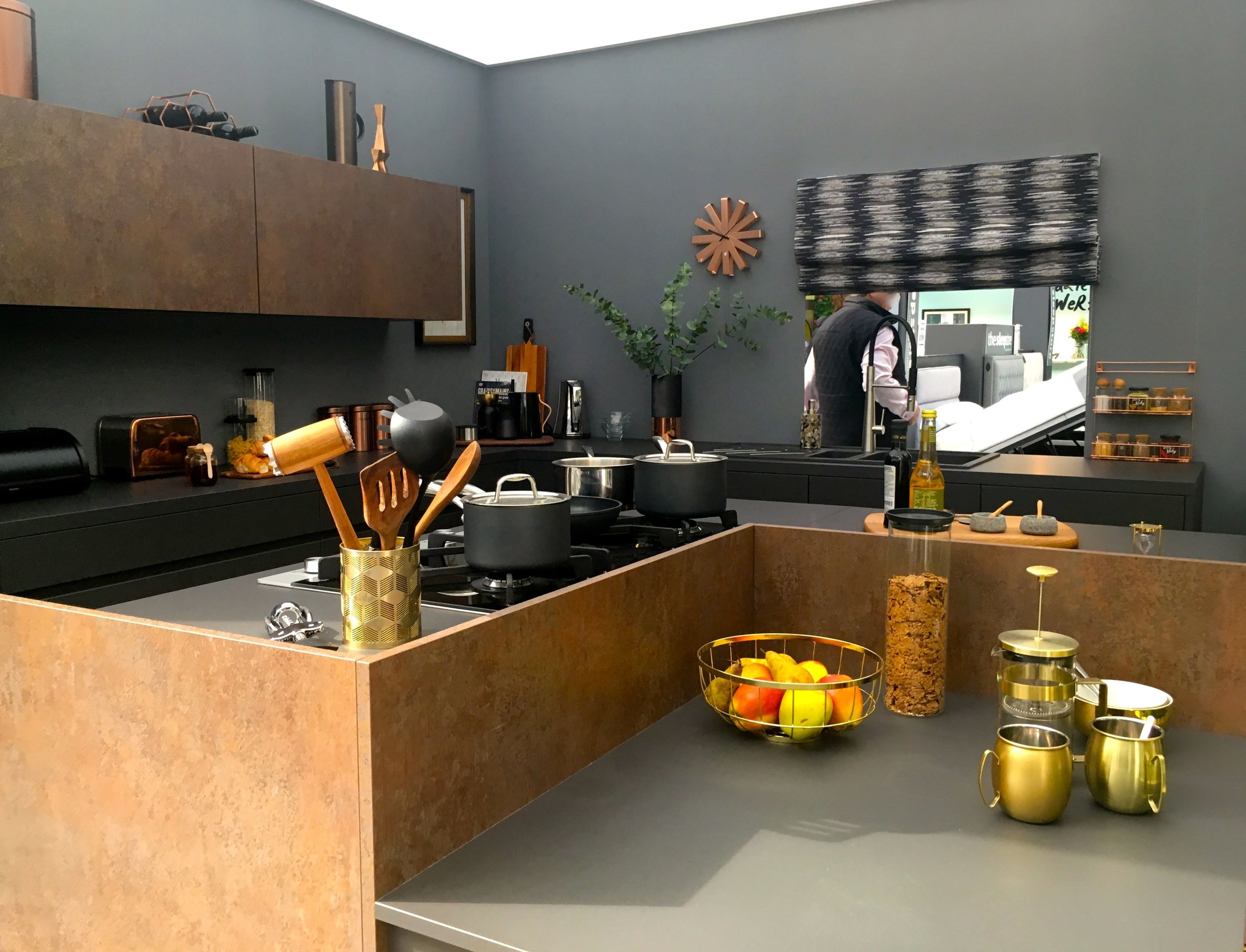 Copper and brass accessories add a pop to a dramatic kitchen