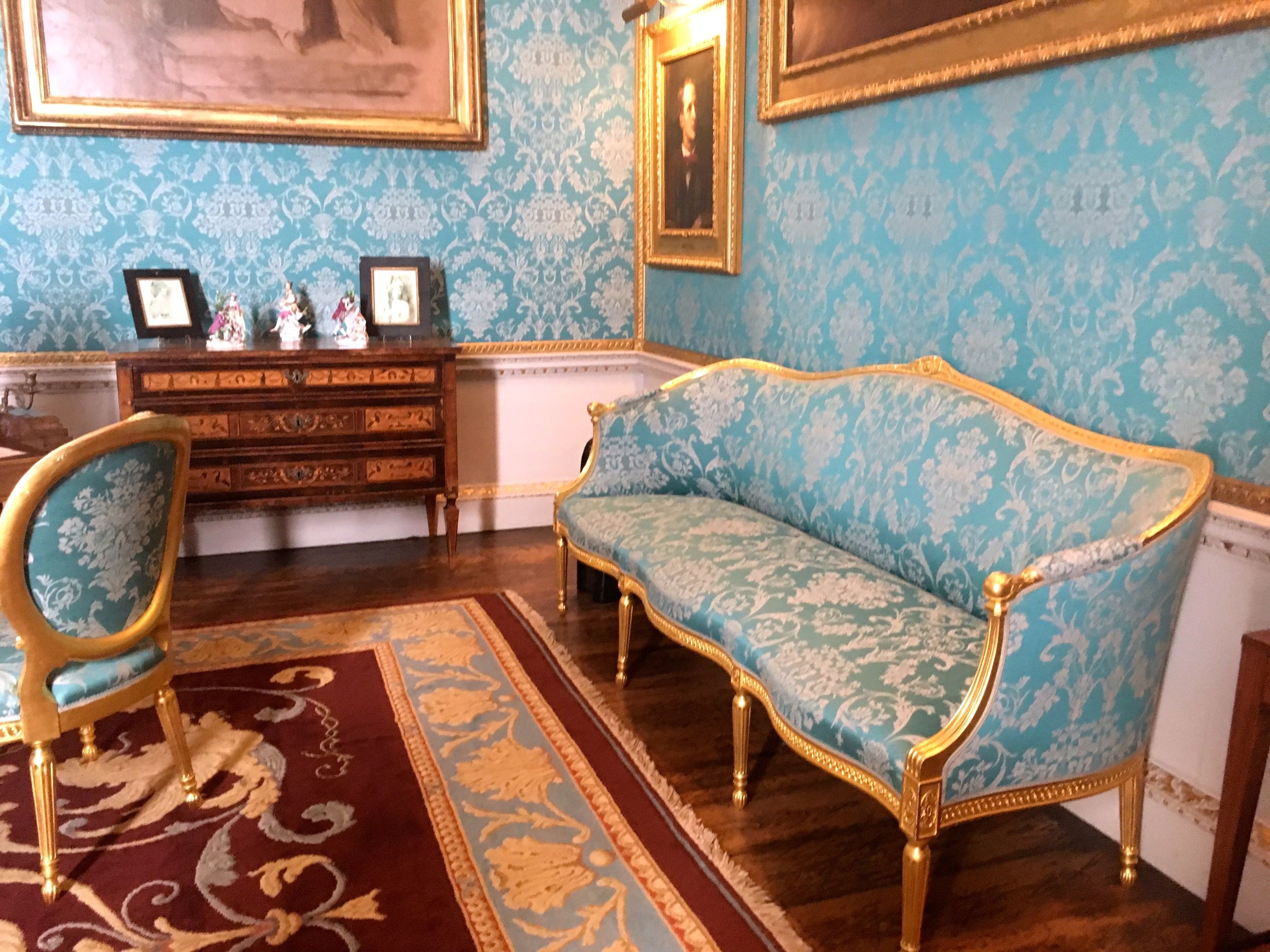 Turquoise and gold upholstered furniture and walls