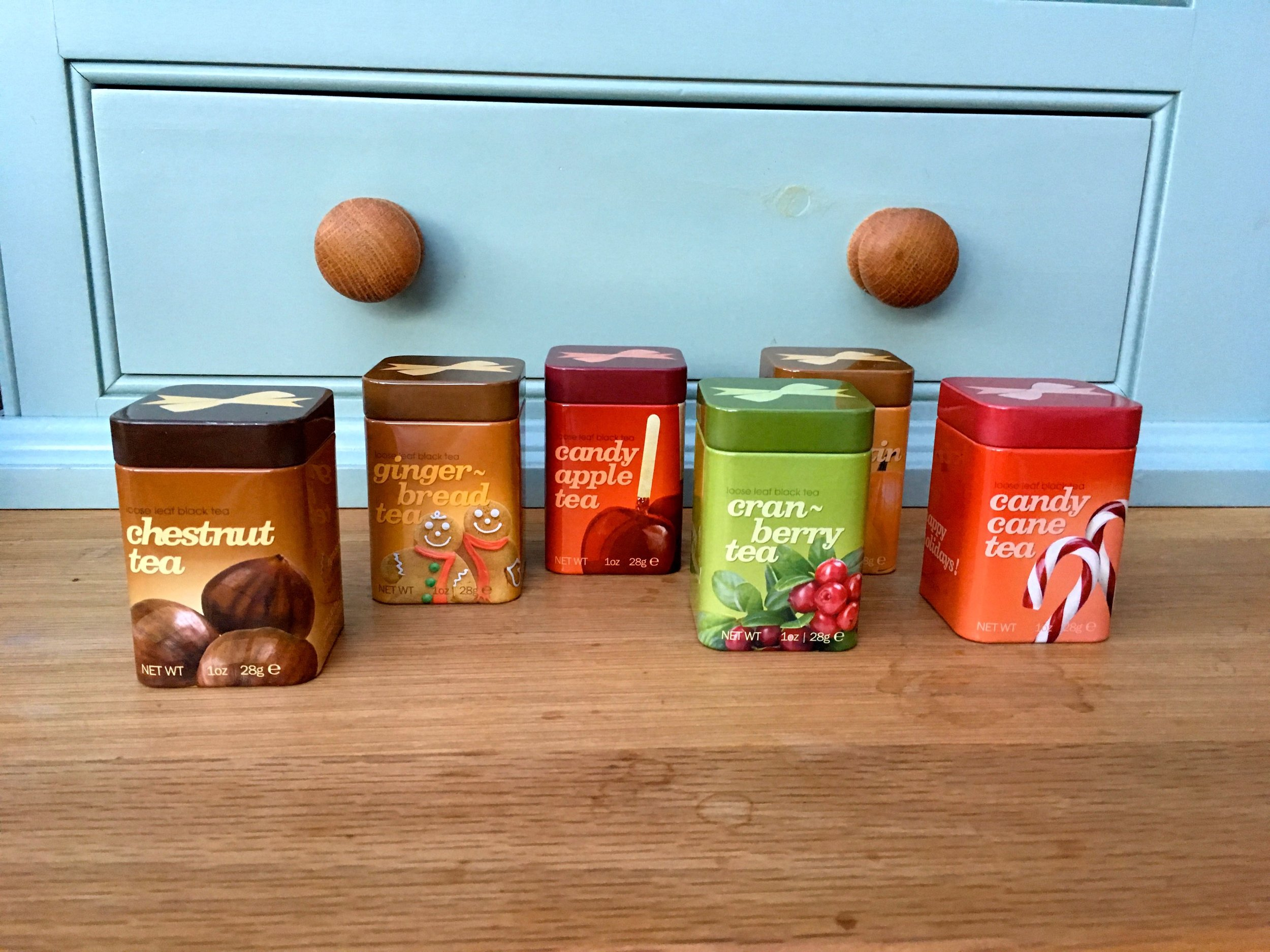 CHESTNUT, GINGERBREAD, CANDY APPLE, CRANBERRY, PUMPKIN AND CANDY CANE TEAS IN MINIATURE TINS, FULL OF HOLIDAY CHEER