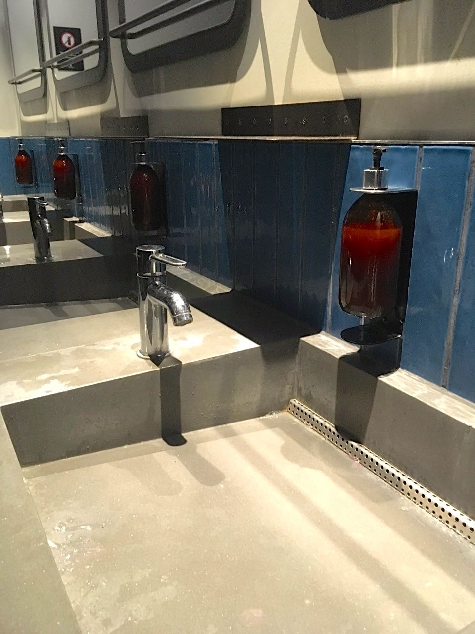 concrete sinks and blue tiles