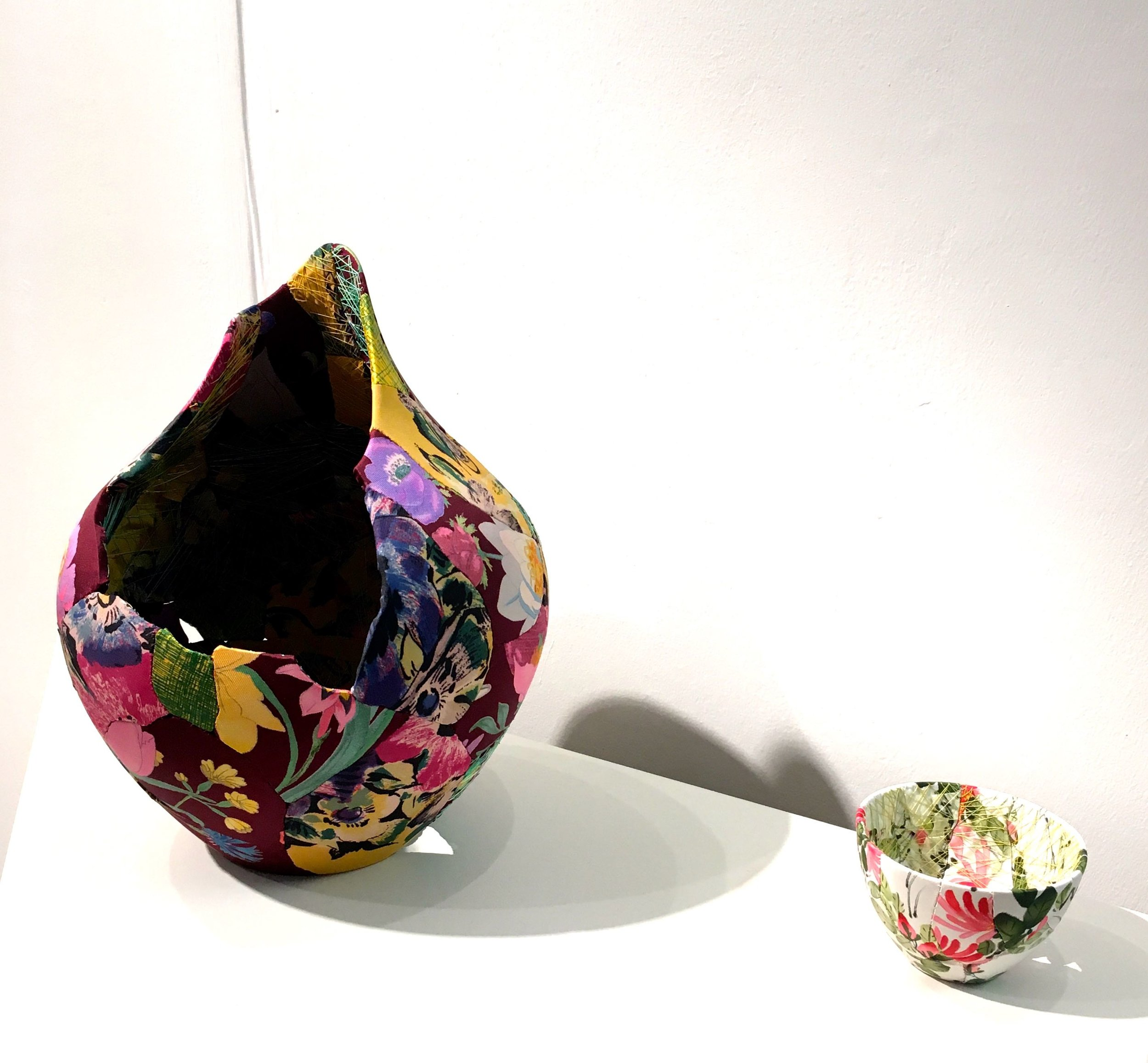 fragments of pottery covered in silk and sewn together to create pieces of art