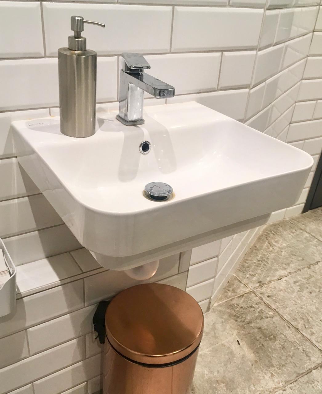 A modern sink and a copper bin