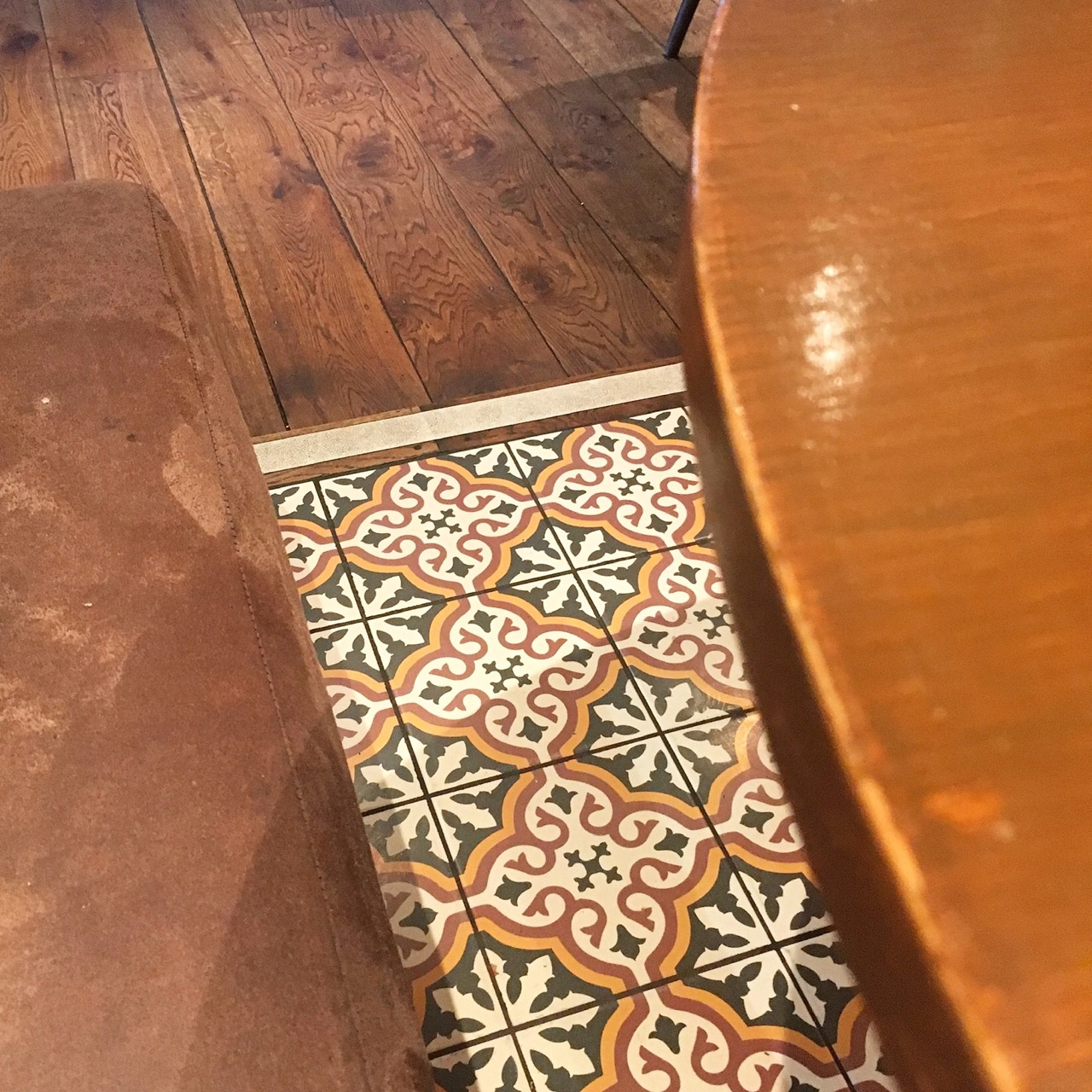 Seating, tiled floors and our table at the Curious Pig