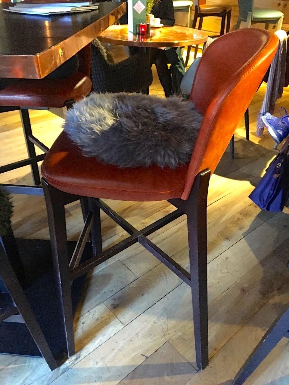 A high bar stool and cosy cushion