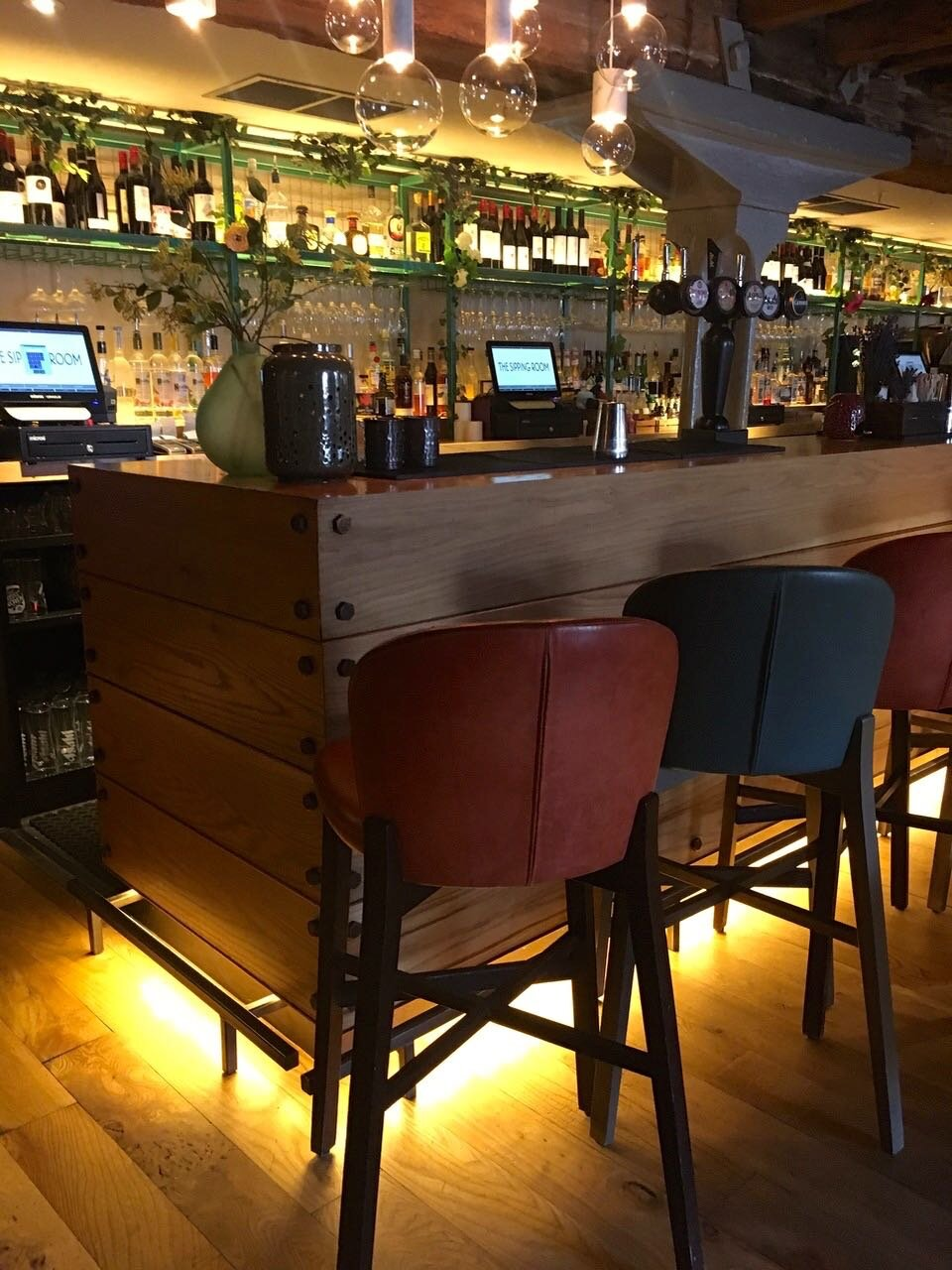 a wooden bar, open shelves and bar stools with clever lighting