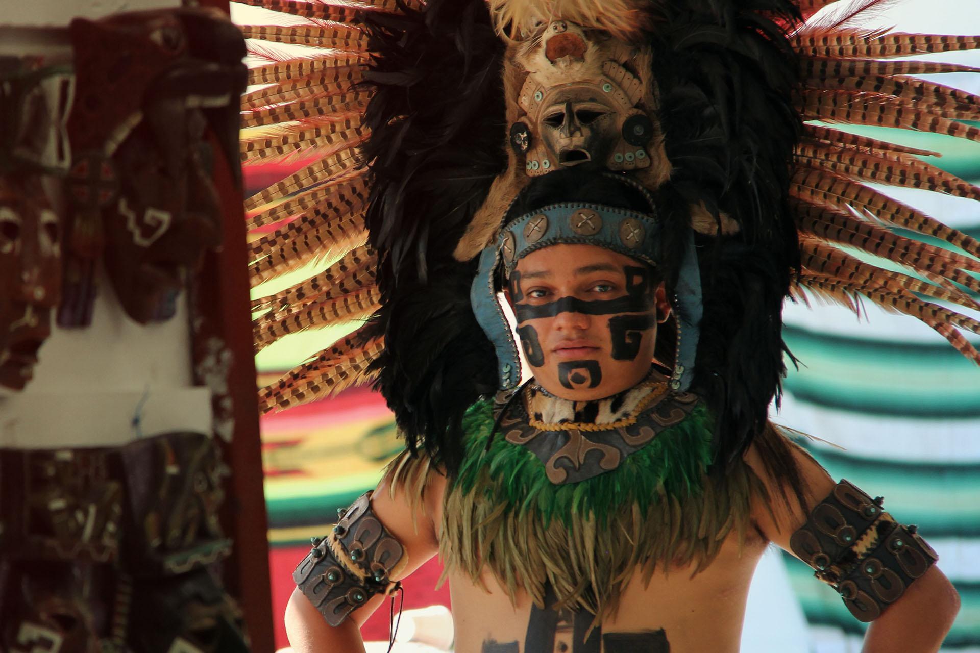 Un local vestido de guerrero maya en el local de artesanías.