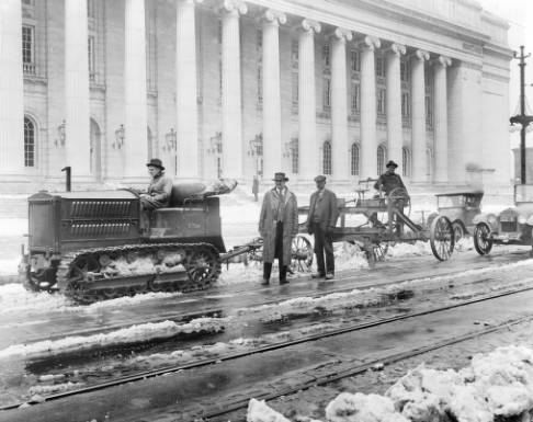 Tractor_and_blade_cleaning_snow_from_streets_near_Post_Office.jpg