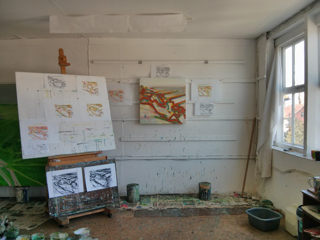 The studio this afternoon. Several oil pastel drawings and charcoal drawings on the wall and the board. After this photograph was taken I added alot of grey to the painting, didn't like it so scraped it all off, repainted the canvas white and painted the network of lines in first yellow, then blue and then red. It now looks more bleached then this.