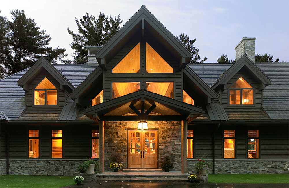 A deep covered entry portico provides shelter while the glow of the interior seen through lofty gable beckons and hints at the interior experience.