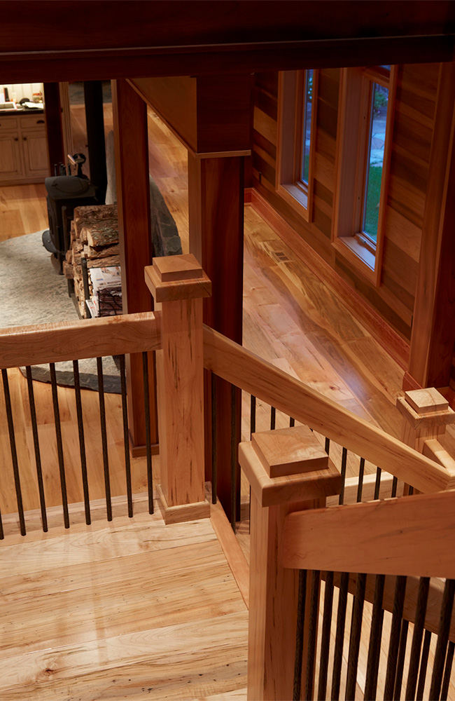 Open riser (species) stairs and rails with wrought iron balusters.