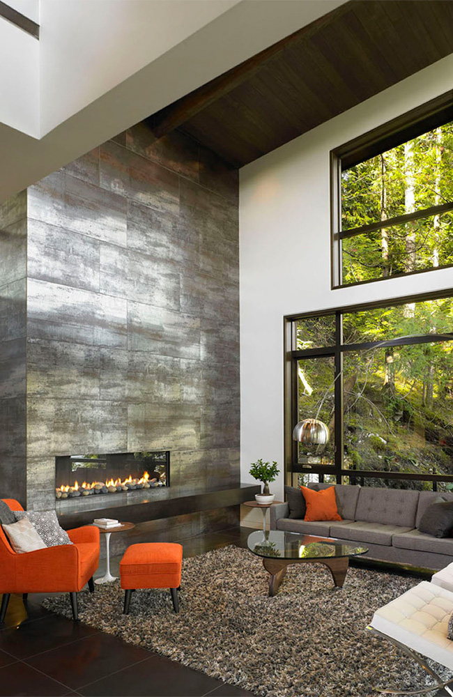 White wall and metallic floor and fireplace surfaces are essentially colorless. By contrast, the verdant hues of nature take center stage. Metaphorically speaking, the message is that human made materials are subordinate to works of nature.