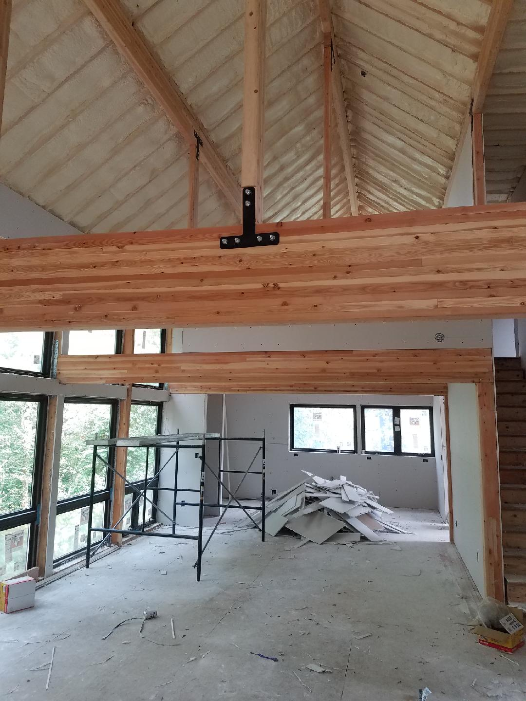 Now sheetrocked, the great room takes shape. Laminated girders and roof beams to the fore!