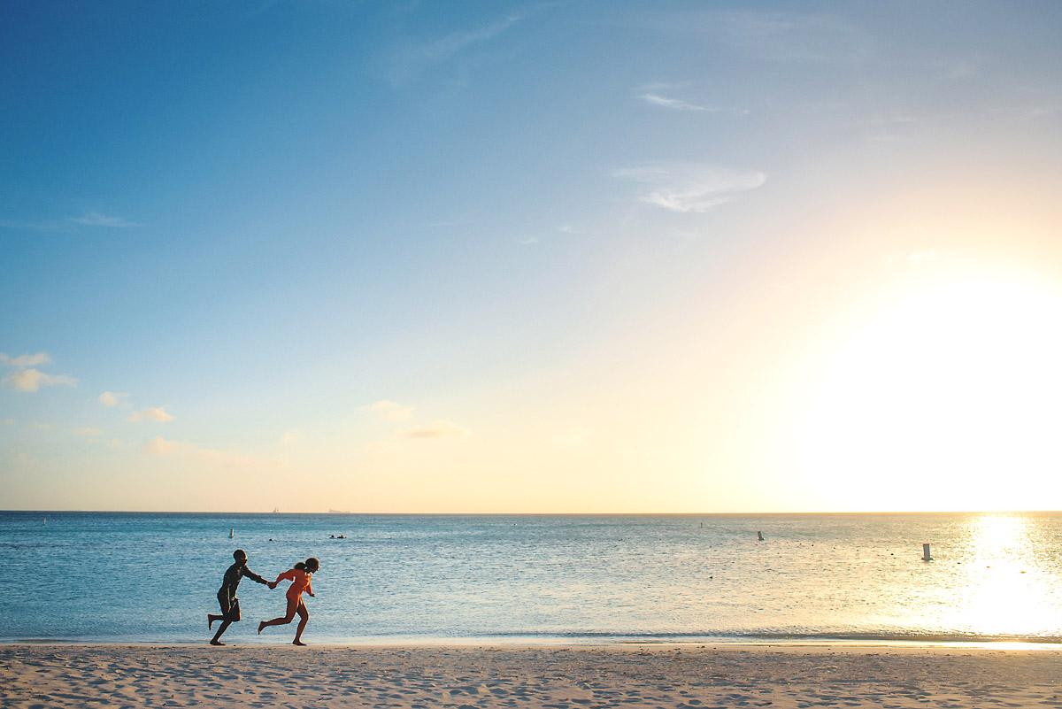 couple running along the beach in aruba- engagment shoot.jpg