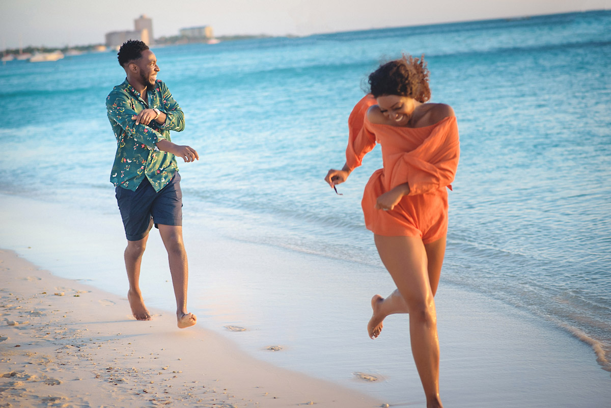 boy chasing girl on beach in aruba- engagment shoot.jpg