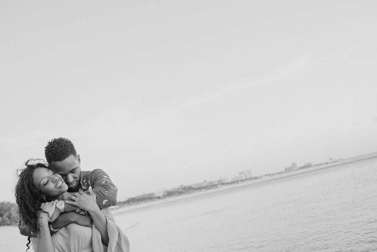 black and white photo of boy holding girl around shoulders and snuggling in aruba- engagment shoot.jpg
