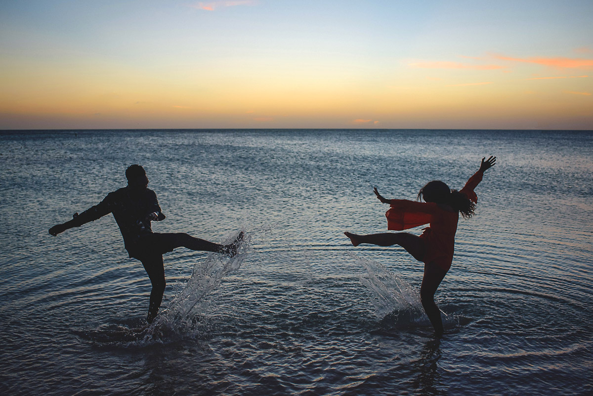 Couple kicking water on beach towards each other in aruba- engagment shoot.jpg