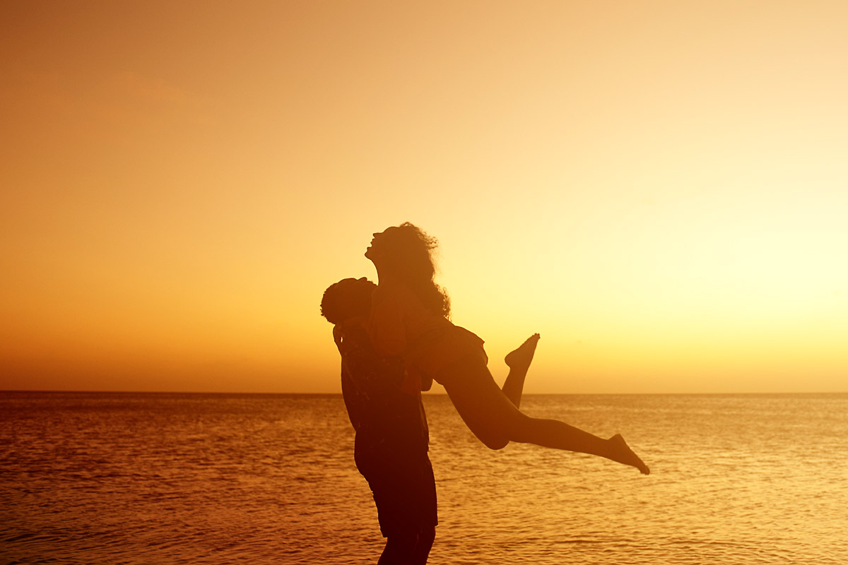 Boy lifts excited girl up on beach in aruba- engagment shoot.jpg