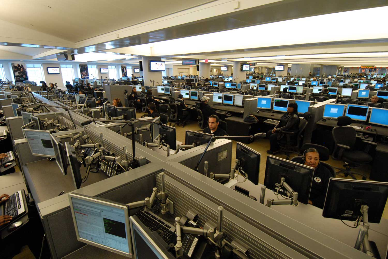 The emergency call center in Brooklyn, where operators are supposed to be aided by a sophisticated computer system upgrade that was supposed to streamline the dispatching of 911 emergency response services.  The system upgrade has been hobbled by technology problems, is many years behind schedule, and is about $1 billion over budget.  Source :  Official Photograph/New York City