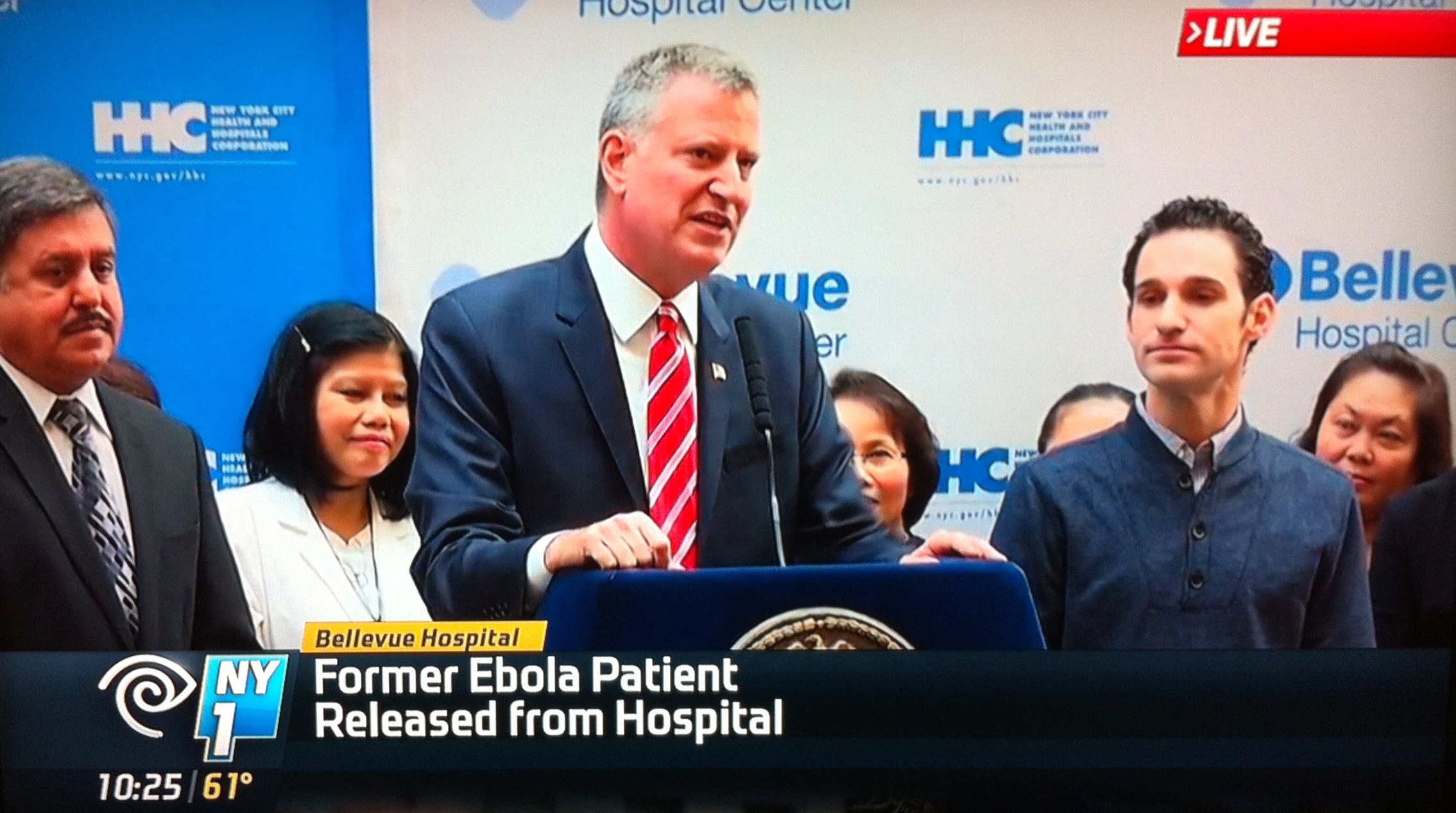 New York City Mayor Bill de Blasio speaking on the occasion of the hospital discharge of Dr. Daniel Spencer, right, the first person to be treated for Ebola in New York City.  Source :  NY1 Screen Shot
