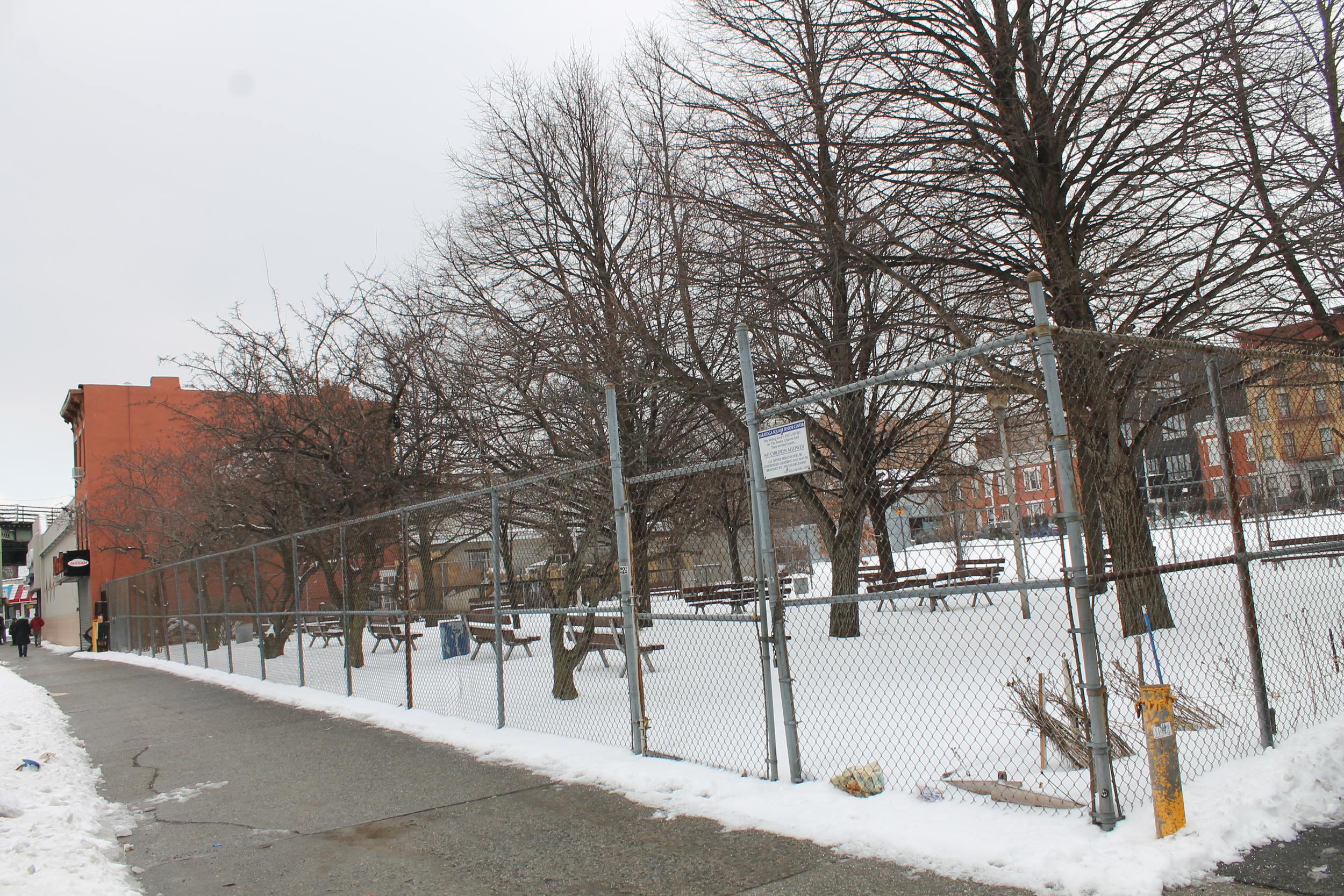 The sale of Saratoga Square included thepark in the foreground, which is adjacent to 930 Halsey Street, and the vast parking lot in the background, which is located along Macon Street, as seen on March 2, 2015. The park and the parking lot are equal to or exceed the size of the footprint of 930 Halsey Street and 55 Saratoga Avenue. Credit : Louis Flores
