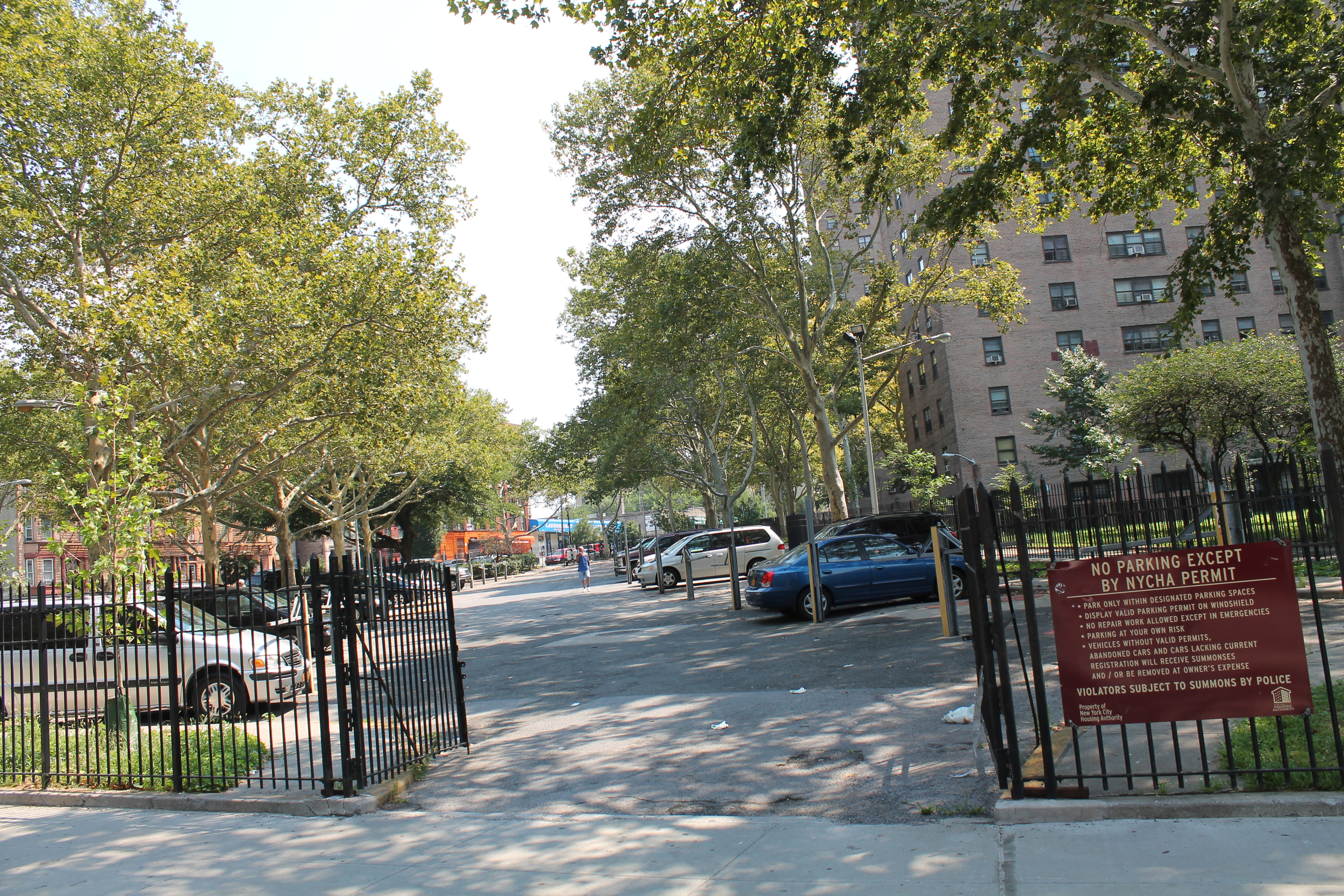 """A gated parking lot at the  Mill Brook Houses  in Mott Haven, The Bronx, as seen on Monday, August 17, 2015.  New York City Housing Authority  CEO  Shola Olatoye  has said that spaces identified for its controversial infill plan to lease open lots on NYCHA properties to private real estate developers can be rationalised, because the proposed sites are """"strewn with trash"""" and not in use. However, the condition of the Mill Brook Houses parking lot was relatively well kept, except for discards that are typically wind-blown from city sidewalks. Source : Louis Flores/Progress Queens"""